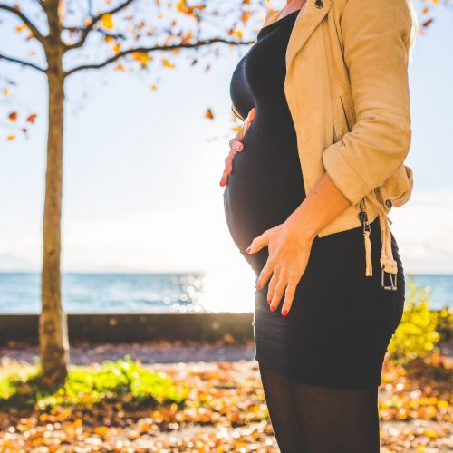 pregnant woman wearing beige long sleeve shirt standing near brown tree at daytime