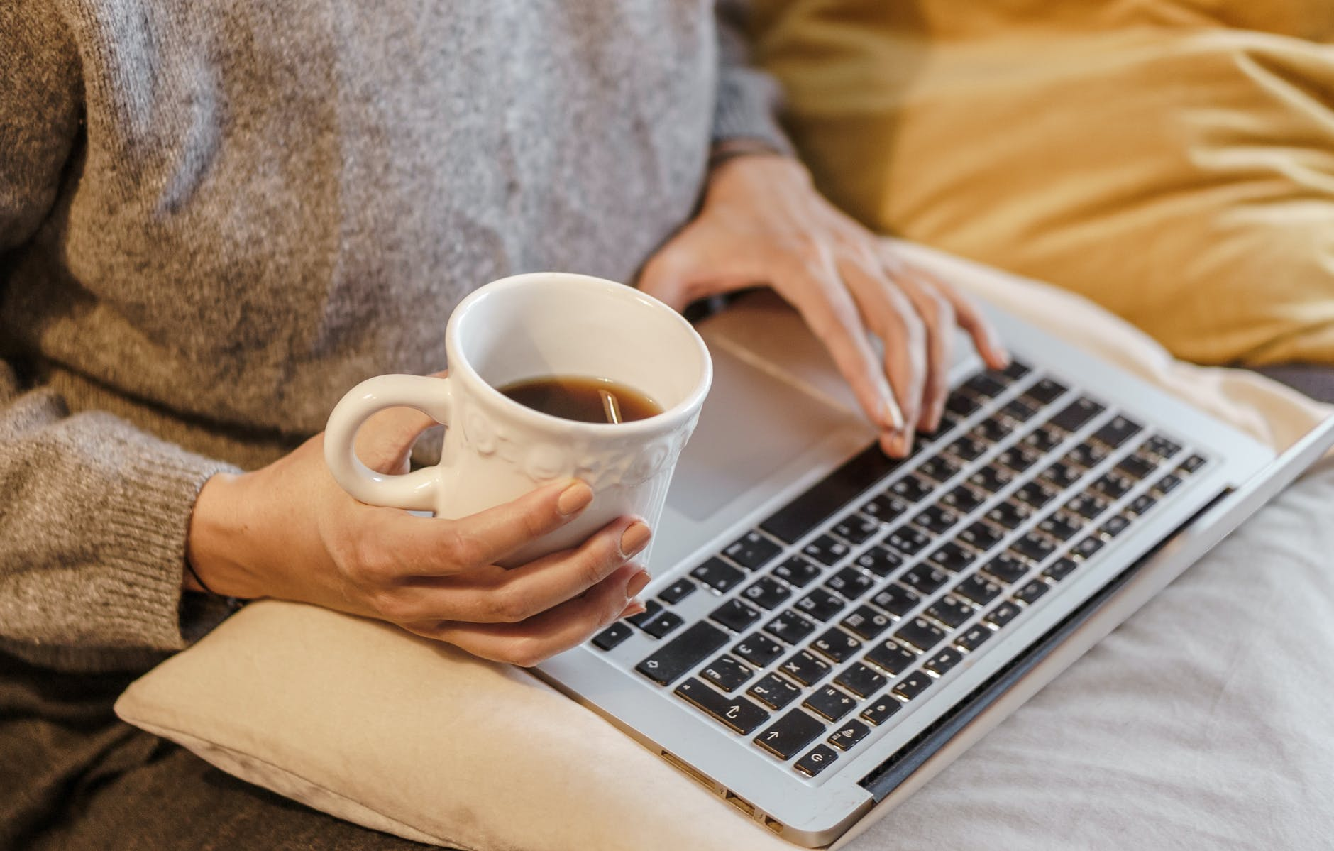 crop freelancer with mug of coffee typing on laptop
