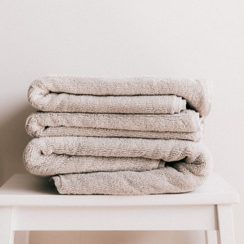 stack of light beige towels on white stool