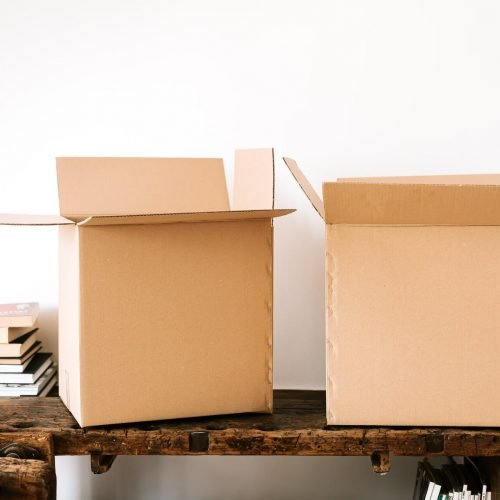 carton boxes and stacked books on table