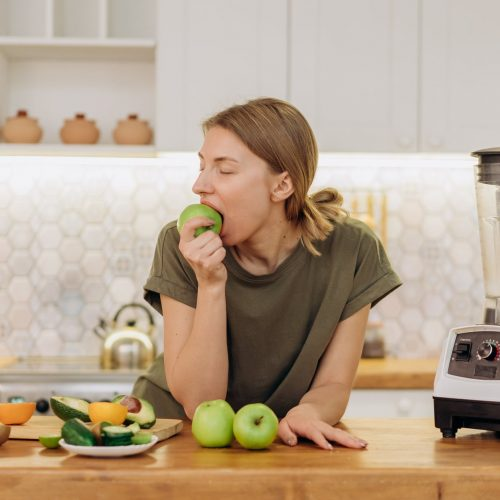 woman in gray crew neck t shirt eating green apple fruit