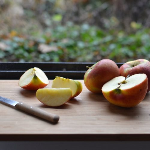 fresh ripe apples placed on wooden chopping board