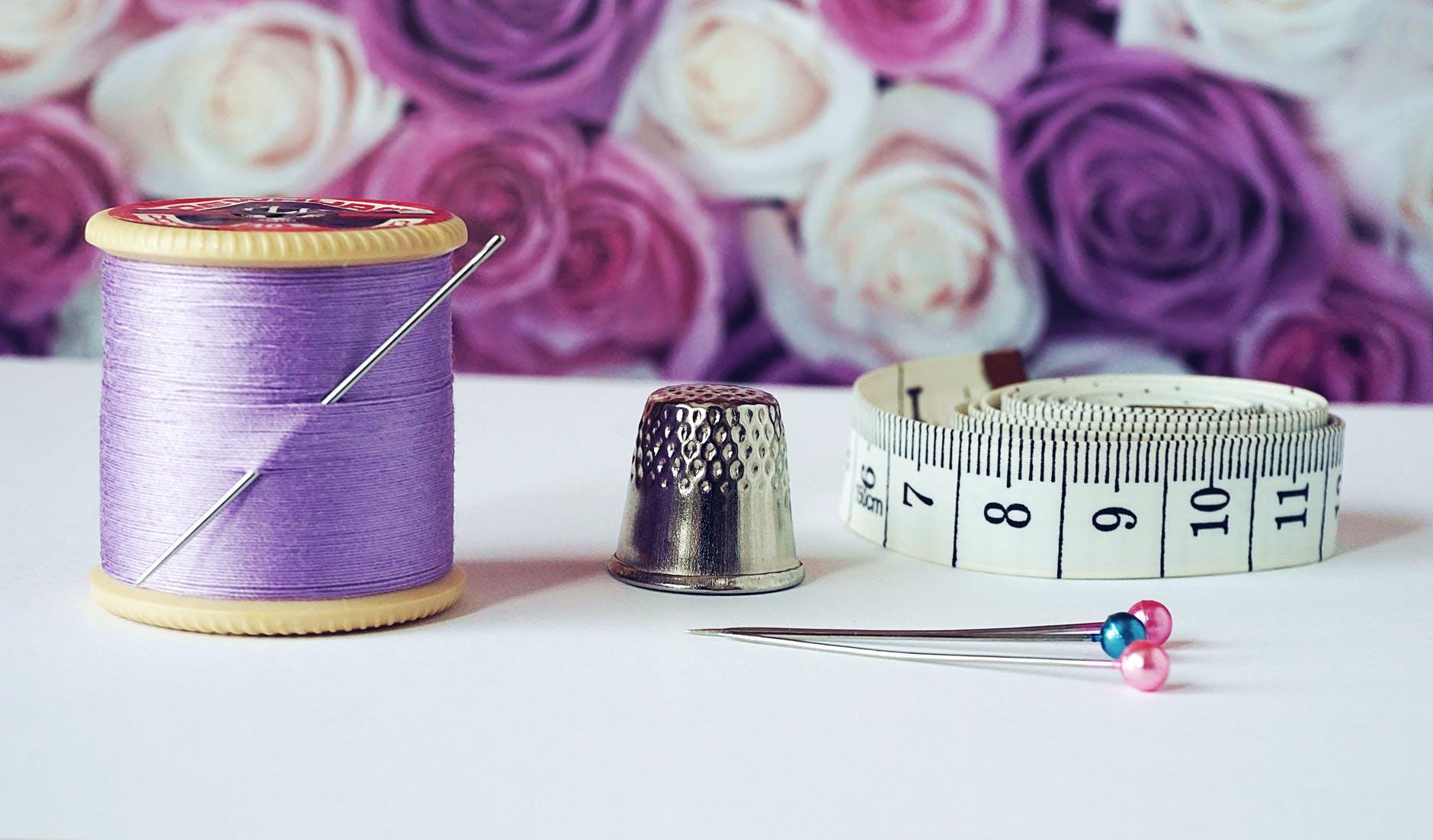 spool of purple thread near needle thimble and measuring tape