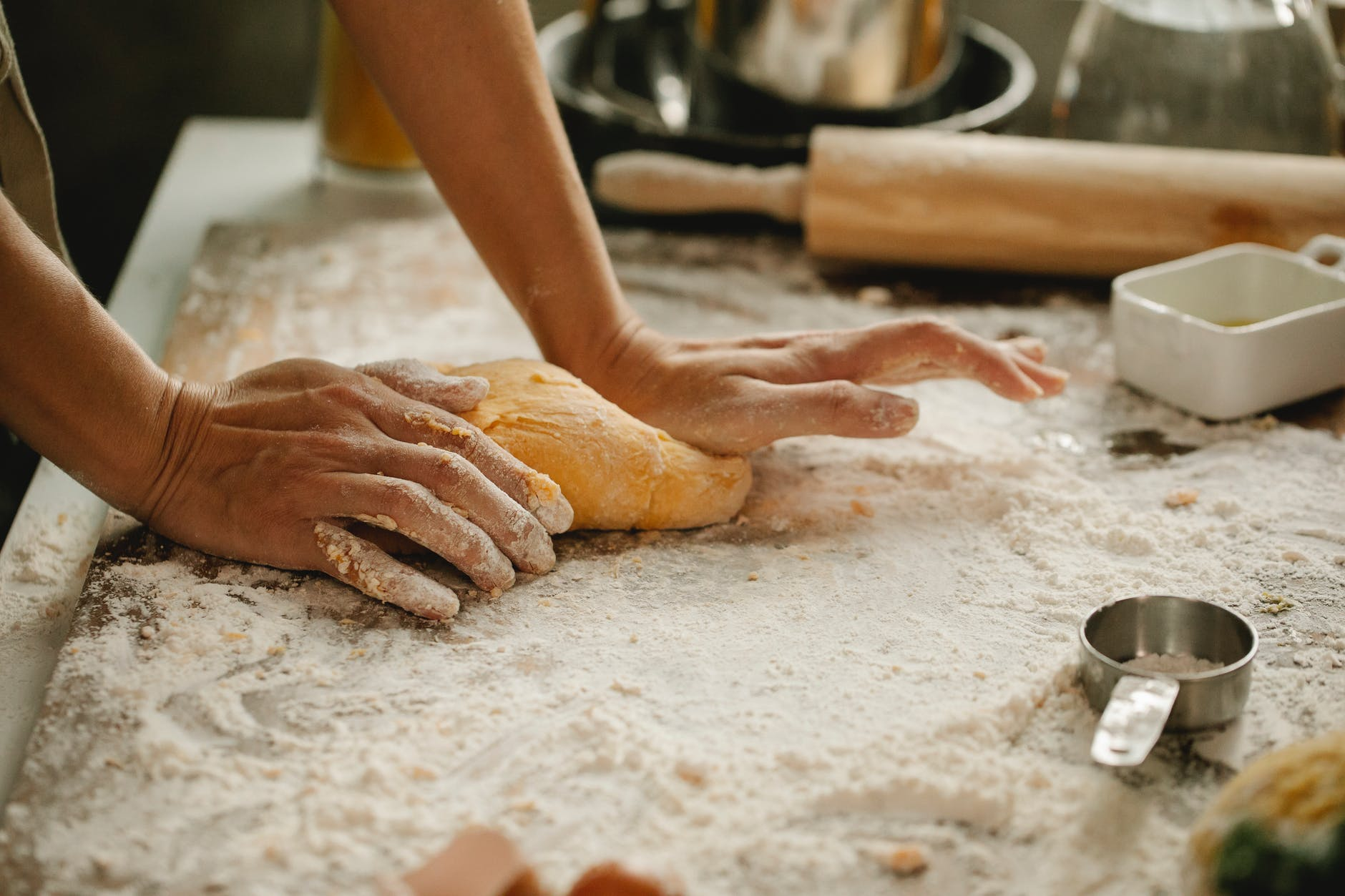 woman making pastry on table with flour